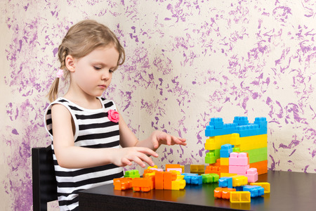 builds: little girl builds bricks at the table