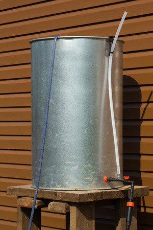 rainwater: chrome barrel of rainwater with hoses for irrigation Stock Photo
