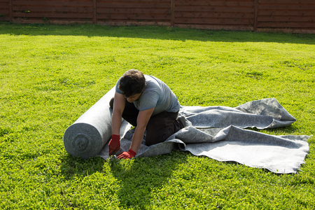 waterproofing material: man cut the geotextile on the lawn