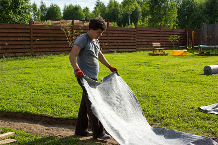 man lay geotextiles in a pit for garden path