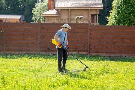 Człowiek kosi trawę z trymerem smyczkową Zdjęcie Seryjne