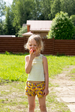 Little girl eats a red apple outdoor Stock fotó