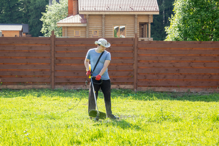 mows: man mows the grass with a string trimmer