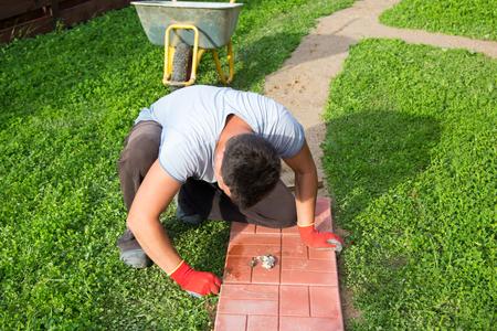 man puts the concrete tiles on the path Stock Photo