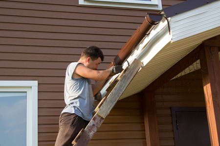attaches: man attaches gutter on the roof of the porch Stock Photo
