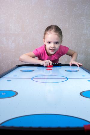 vehemence: Little girl is playing in an air hockey