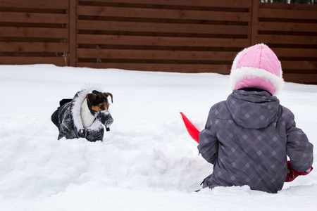 Girl and dog playing in the snow with a shovel