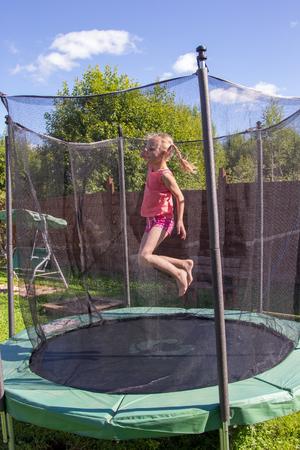 fille sautant sur un trampoline derrière un filet de protection Banque d'images