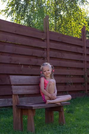 pensativa niña sentada en un banco de madera Foto de archivo