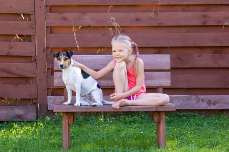 girl with her dog sitting on a wooden bench