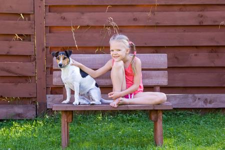 Mädchen mit ihrem Hund sitzt auf einer Holzbank