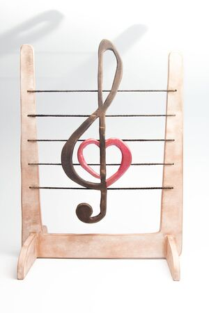 wooden figurine of a treble clef on a stave
