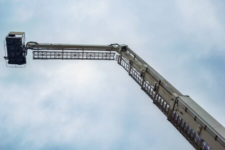 telescopic lift of a fire truck on sky background Stock Photo