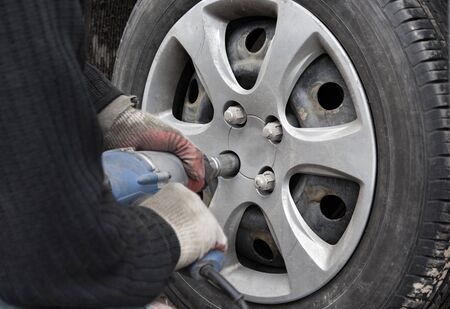 technician unscrews nuts on a wheel with a pneumatic screwdriver