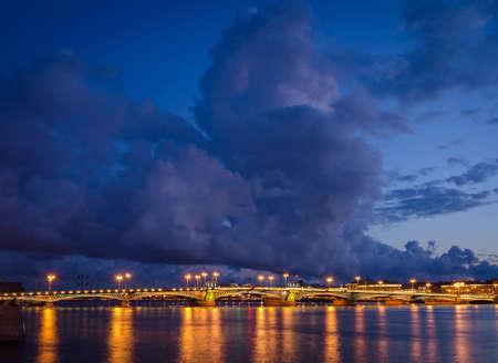 Night cityscape with river and bridge in Saint-Petersburg. Lantern lights on the bridge. Stock Photo