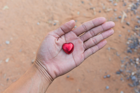 youngs: Red heart chocolate in youngs hands.