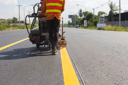 infra construction: Machine eject and worker on road and traffic sign painting.