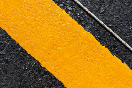 yellow line: Asphalt road as abstract background, yellow line on the road texture.