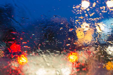 kropla deszczu: Rozmyty samochód sylwetka widziana przez krople wody na przedniej szybie samochodu.