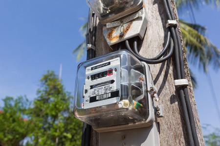 electric meter: Contador eléctrico en poste eléctrico.