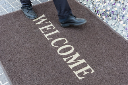 office shoes: Close up new doormat of welcome text. Stock Photo