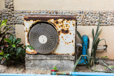 Old rusty air conditioner is located behind the building.