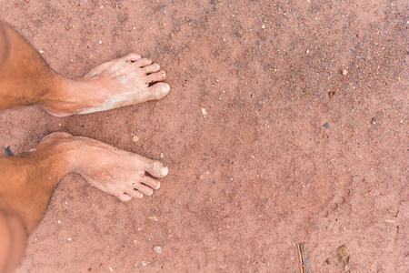 long toes: Closeup of feet muddy on the floor.