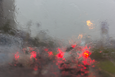 Blurry car silhouette seen through water drops on the car windshield.