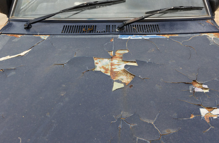 Old car paint broke off,cause is rusted steel surface of car.