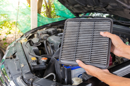 Technician holding dirty air filter for change a new air filter in a car. 写真素材