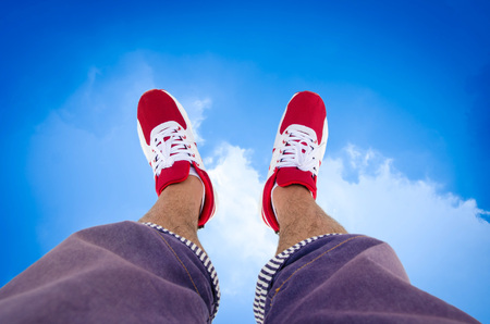 feet crossed: shoe of a man who is , blue sky, white clouds