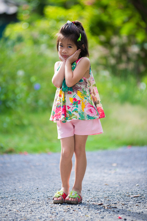 Pensive daughter shy and looking at camera isolated on a green background Stock Photo