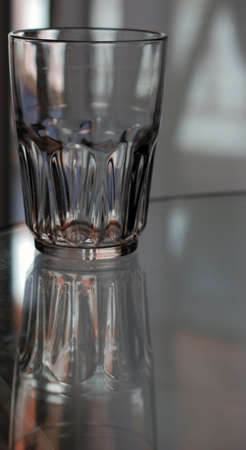 An empty glass sits with its reflection on a glass table.