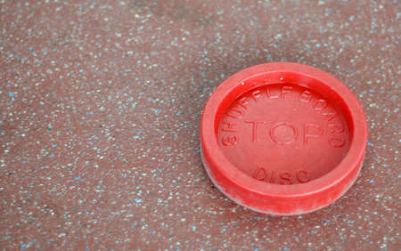 A lone red shuffleboard disc sits on the ground.