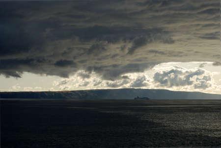 Storm clouds gather over a ship at sea. Reklamní fotografie