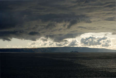 Storm clouds gather over a ship at sea. photo