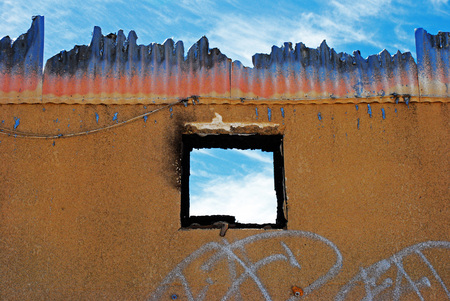 Blue sky through window of burnt out building