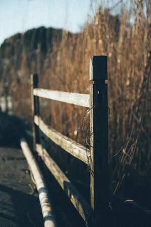Old wooden guardrails by the lake.