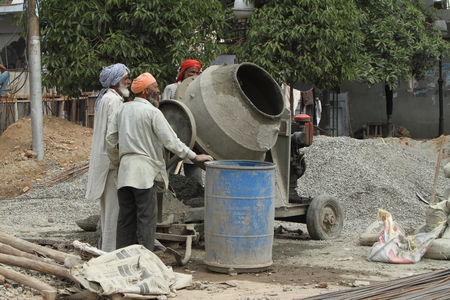 upturn: Indian construction workers are working and building a house