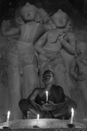 luz de velas: monje budista en la oraci�n por la luz de las velas