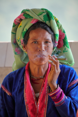 smoking a cigar: Old woman from Burma smoking a cigar Editorial