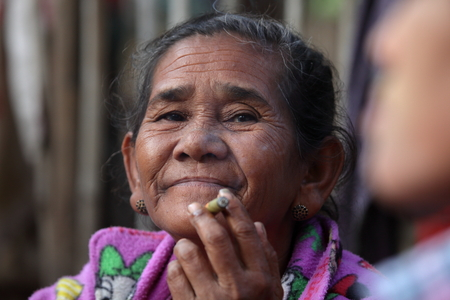 smoking a cigar: Old woman from Burma smoking a cigar Stock Photo