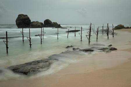 The stilt fishermen at Koggala Beach in Sri Lanka Stock Photo
