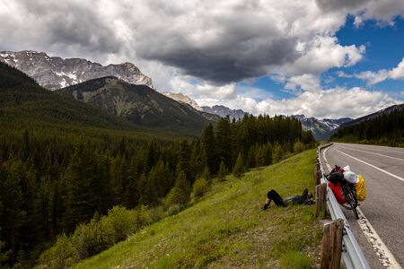 Cycling and relaxing along a road in the Rocky Mountains