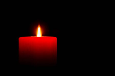 A red candle in the dark Stock Photo