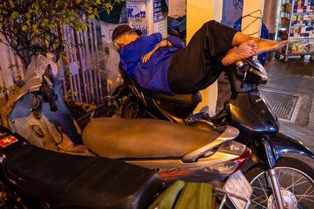 A sleeping man on a motorcycle in Vietnam