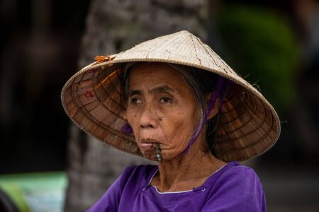 Old woman from Vietnam is smoking a cigar Stok Fotoğraf