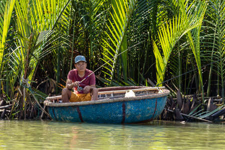 Traditional fisherman is fishing in Hoi An Vietnam in a traditional basket boat
