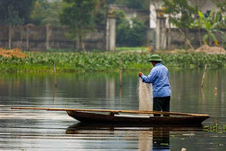 A man fishing in a lake at Ninh Binh in Vietnam