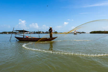A traditional fisherman is throwing a fishing net at Hoi An in Vietnam